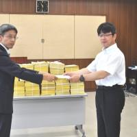 川又労働基準部長に、最賃行政に関する要請書を手渡す、連合福島最低賃金対策委員会 生亀委員長。後ろにあるのは県内から寄せられた署名用紙